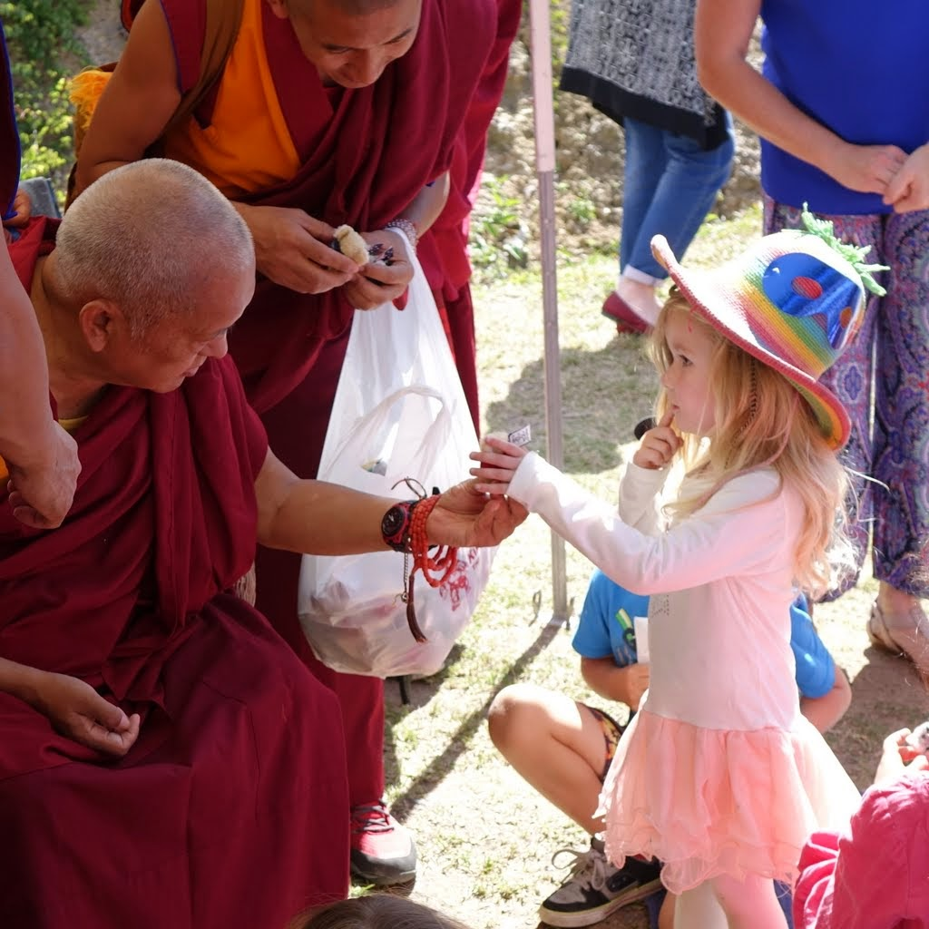 Lama Zopa Rinpoche giving the children little koala bears holding little OM MANI PADME HUNG flags during 40th anniversary celebration at Chenrezig Institute, Australia, September 2014. Photo by Ven. Roger Kunsang.
