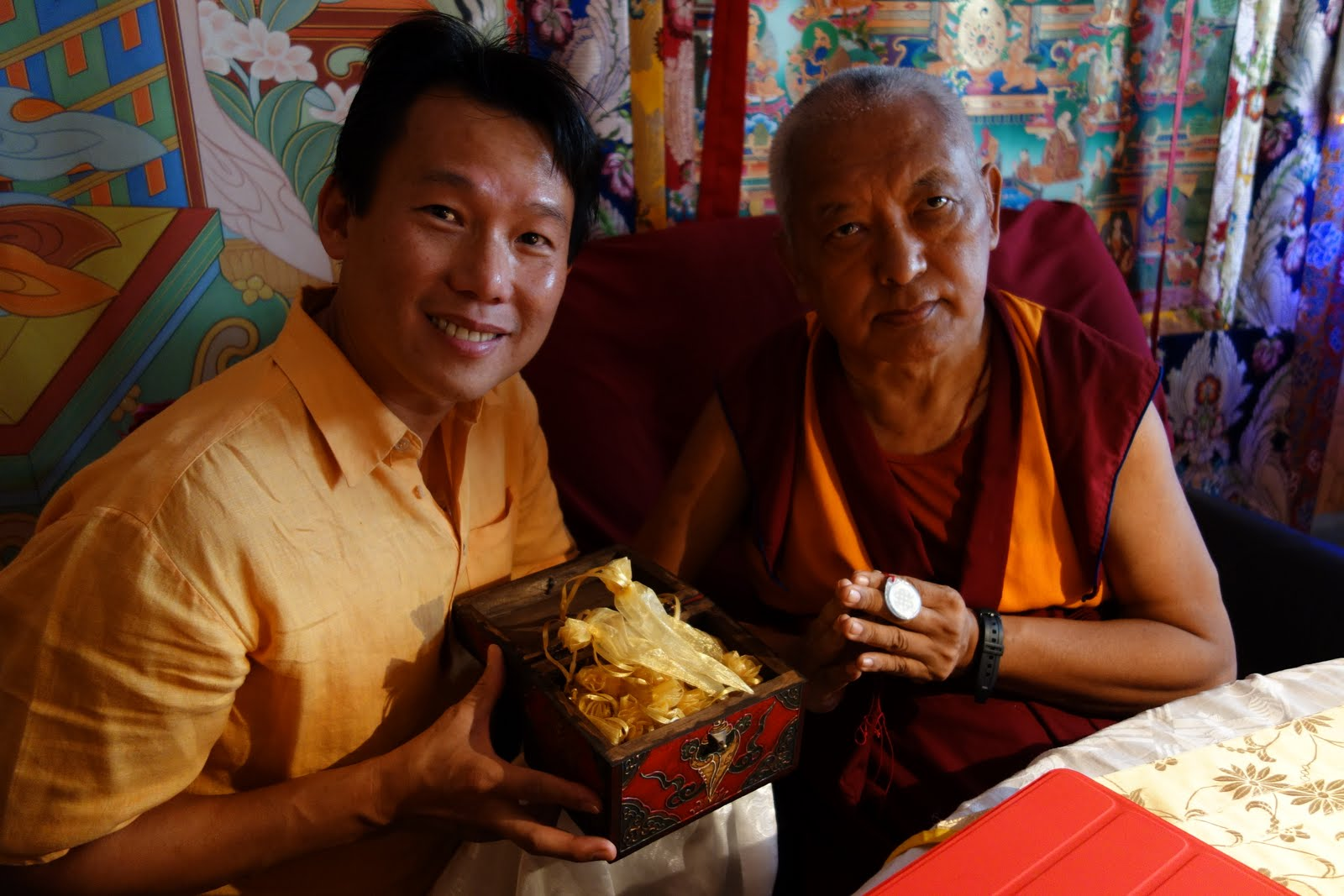 Fred Cheong is offering to Rinpoche a medallion smaller than a nickel with 1,000 Namgyalma mantra's on it . Delicately micro engraved, Rinpoche is holding in his hand. Photo Ven. Roger Kunsang.