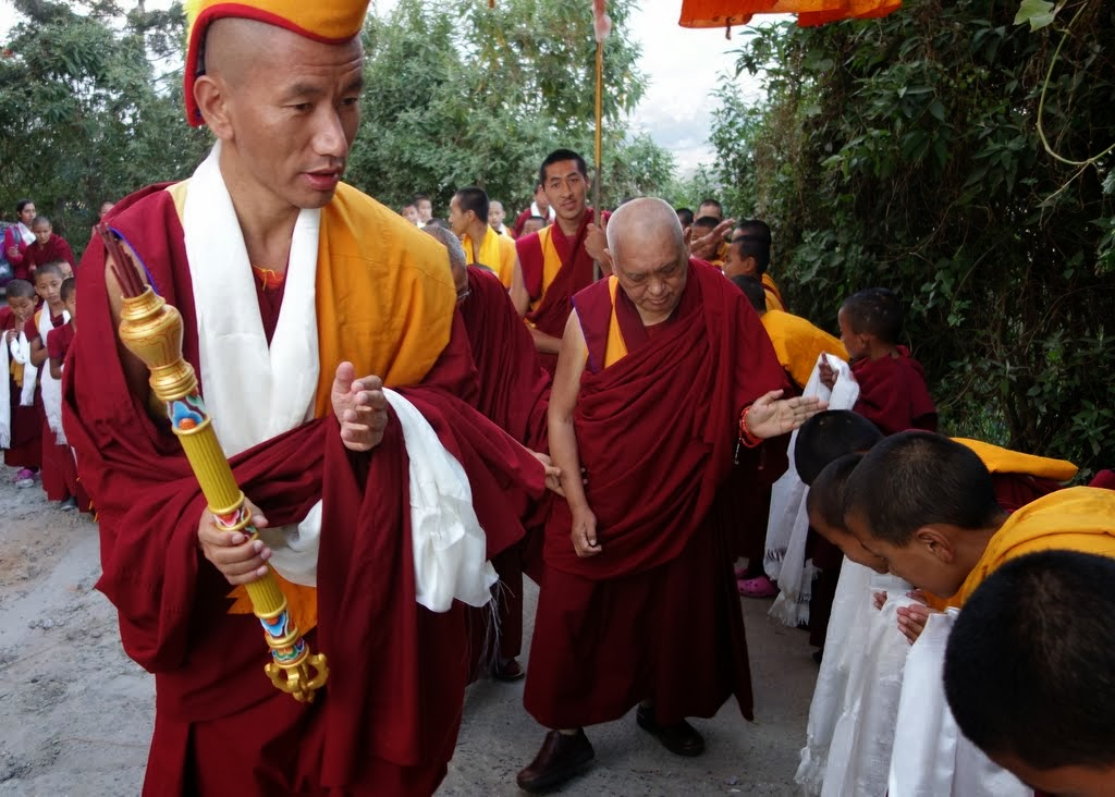 The Kopan gegö (disciplinarian) leads Rinpoche as he arrives at Kopan Monastery and is greeted first by the young monks, Nepal, November 22, 2013. Photo by Ven. Roger Kunsang.