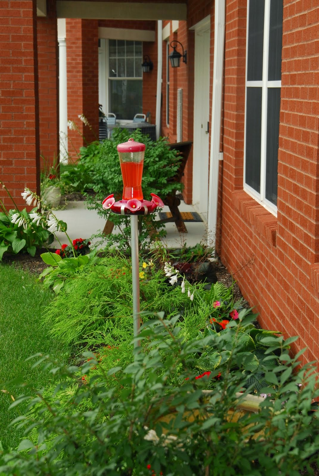 Flowers and hummingbird feeder grace the entrance of a Crest View apartment