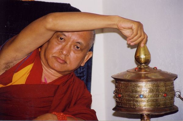 Lama Zopa Rinpoche turning a large hand-help prayer wheel.