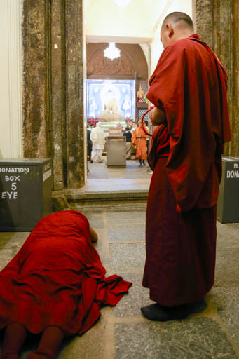 Lama Zopa Rinpoche doing prostrations inside the Mahabodhi Stupa, Bodhgaya, India, February 2015. Photo by Ven. Thubten Kunsang.