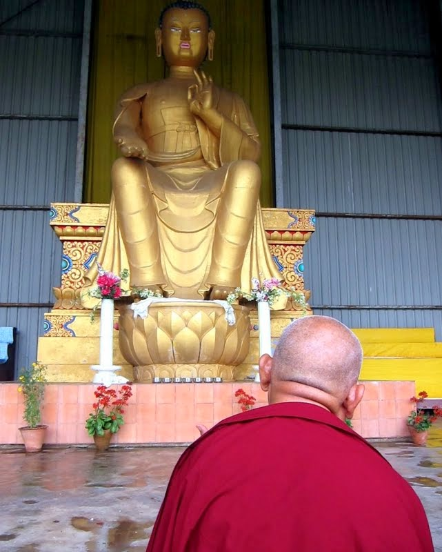 Lama Zopa Rinpoche doing prayers in front of the 24-foot (7-meter) Maitreya Buddha statue on the Maitreya Project land in Bodhgaya, India, February 2014. Photo by Ven. Sarah Thresher.