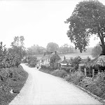 George and Dragon. Looking down the village lane from the railway bridge toward the inn, with Upton Lodge in the distance on the hill. Reproduced by permission of English Heritage NMR.