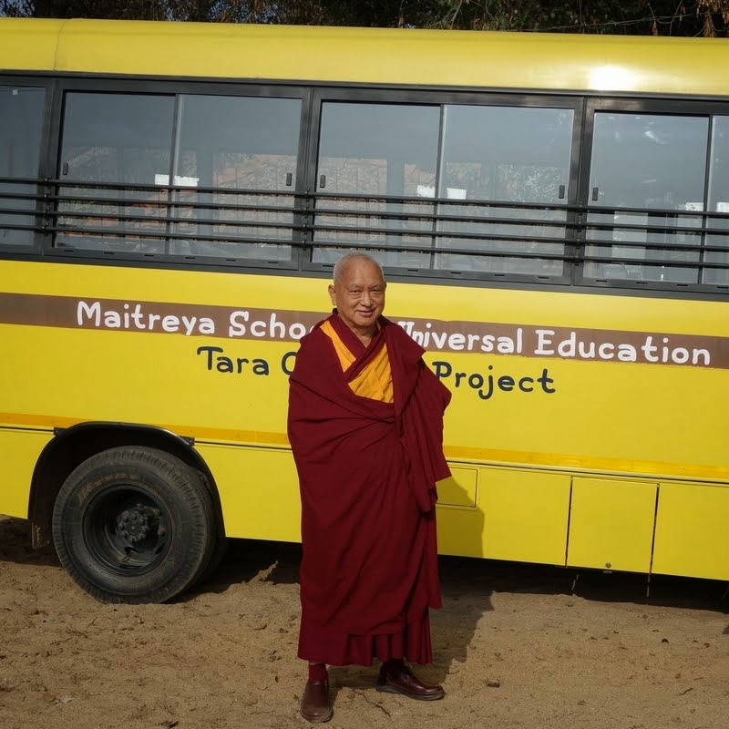 Lama Zopa Rinoche in front of the new bus that serves Maitreya School students and the children who are part of Tara Children's Home, Root Institute, Bodhgaya, January 2014. Photo by Ven. Roger Kunsang.