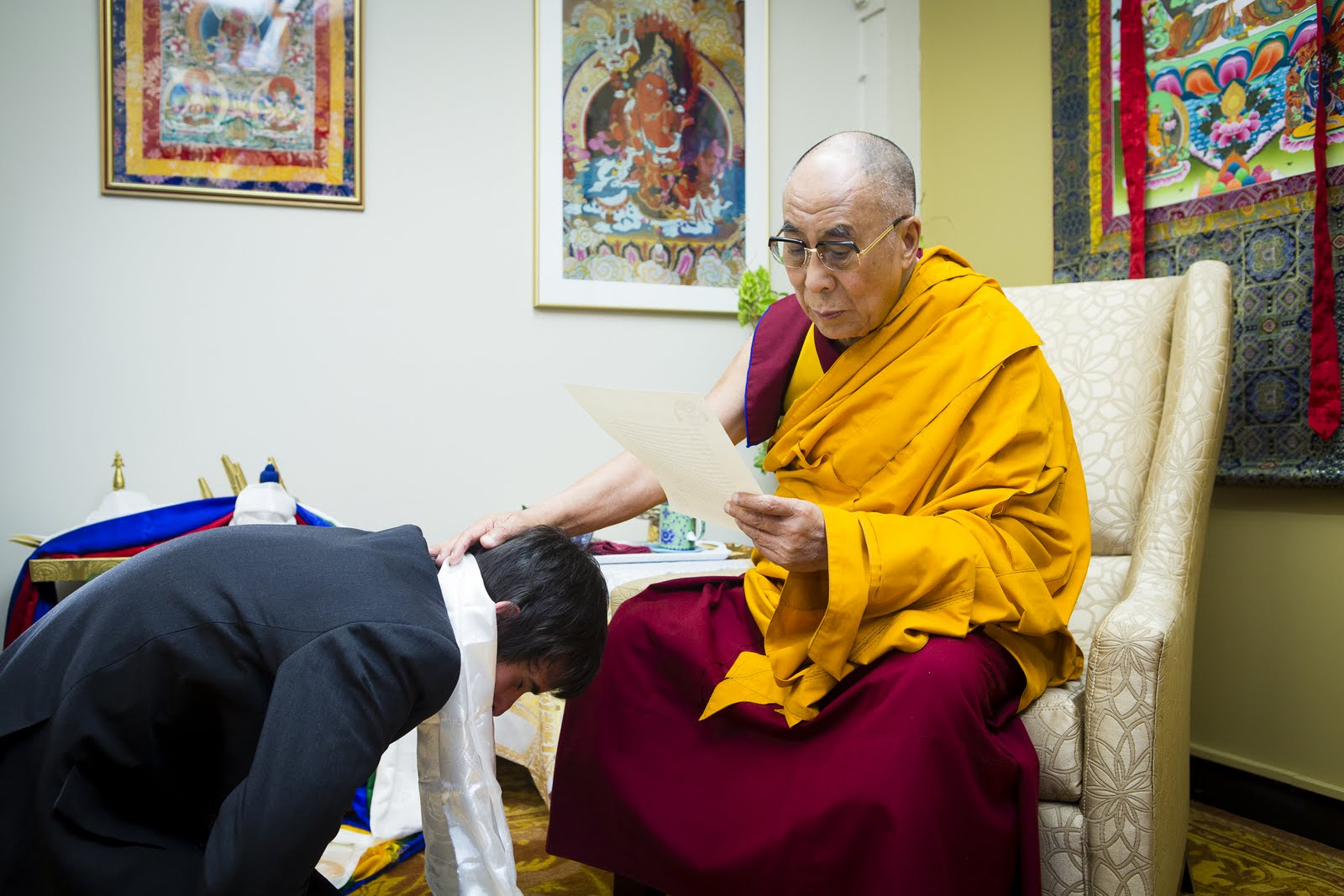 Ösel offering body, speech, and mind mandala to His Holiness the Dalai Lama. His Holiness is reading a letter from Lama Zopa Rinpoche. Photo by Leah Nash.