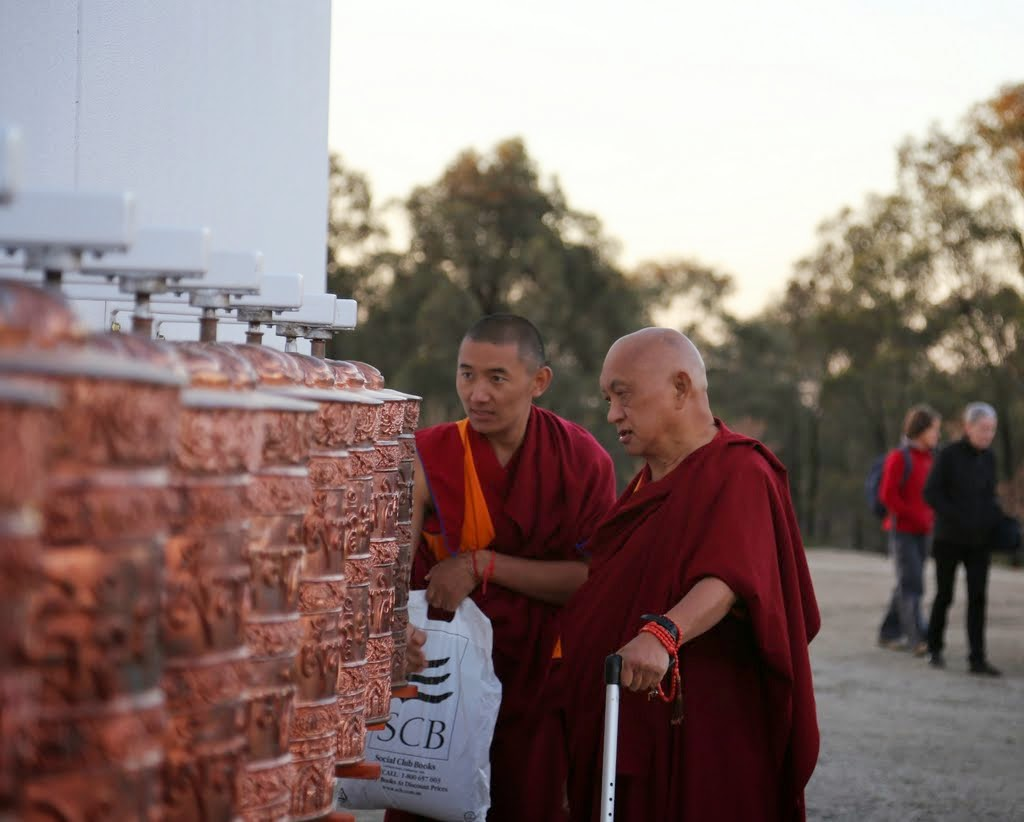 Lama Zopa Rinpoche turning the prayer wheels outside the Great Stupa at dusk, Australia, September 12, 2014. Photo by Ven. Thubten Kunsang.