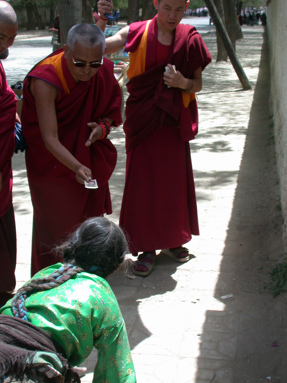 Offerings being made to someone prostrating in Tibet