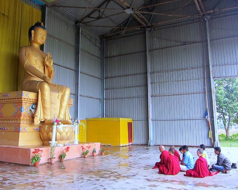 Lama Zopa Rinpoche doing prayers in front of the 24-foot (7-meter) Maitreya Buddha statue on Maitreya Project land in Bodhgaya, India, February 2014. Photo by Ven. Sarah Thresher.