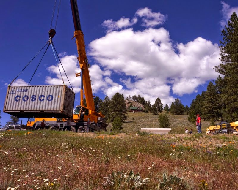 A crane lifts the container that holds the Amitabha Buddha statue and throne, which will be place on a base created by Ven. Yarphel who watches the unloading, Buddha Amitabha Pure Land, Washington, US, July 1, 2014. Photo by Merry Colony.