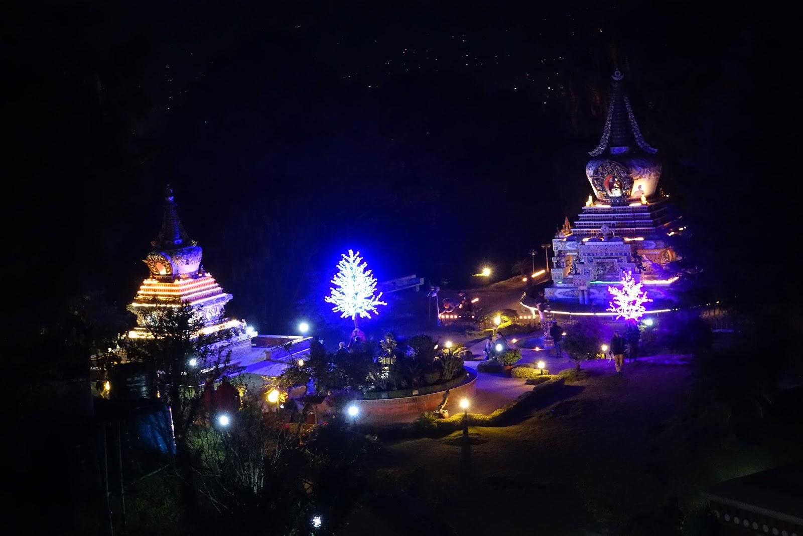 Kopan Monastery at Night, Khensur RinpocheLamaLhundrup'sstupatotheleftandGesheLamaKonchog'sstupatotheright andnewlightofferings onthetrees, Nepal, December 2014. Photo by Ven. Roger Kunsang.
