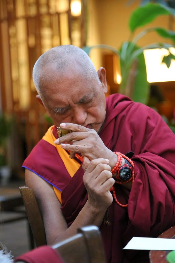 Lama Zopa Rinpoche blessing an item for a small child, Portland, Oregon, US, April 2014. Photo by Ven. Thubten Kunsang.