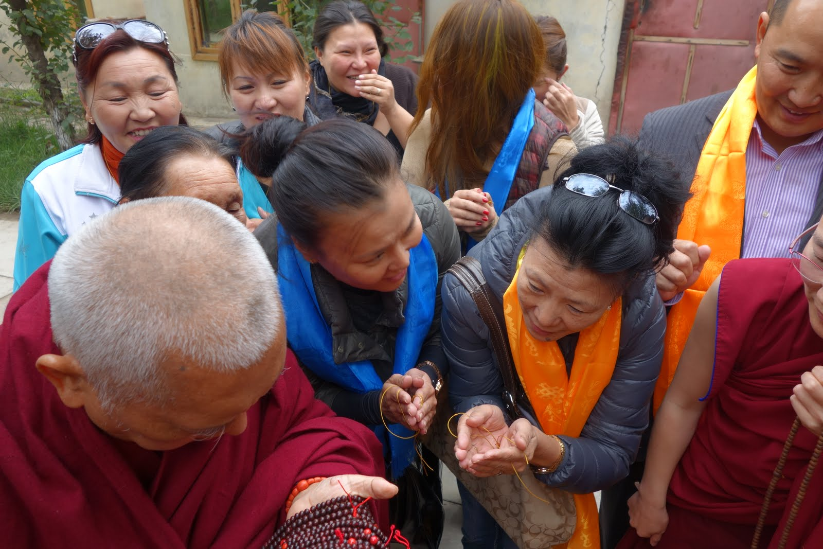 Rinpoche giving out malas and blessing cordss to local people near the Drolma Community Center, Mongolia. September 2013. Photo by Ven. Roger Kunsang