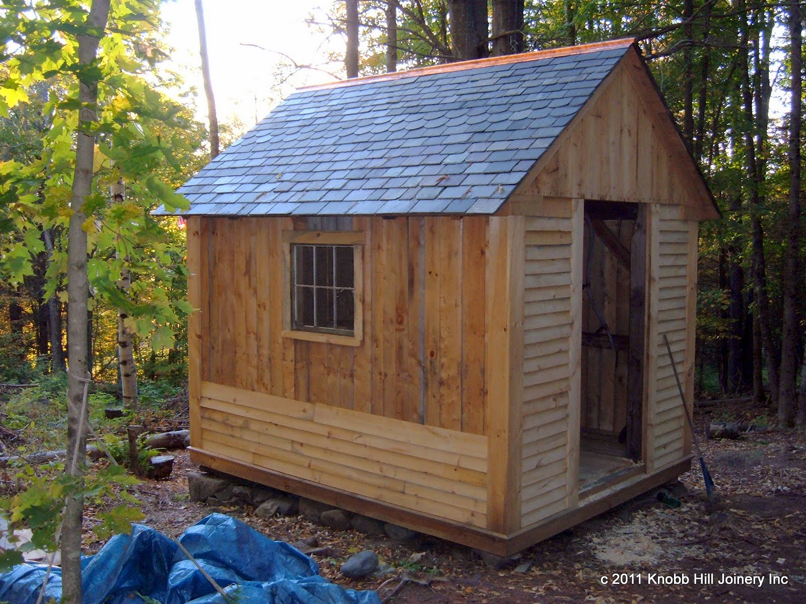 Here is the shed at its final resting place.  With the slate roof and copper ridge in place it nears completion.