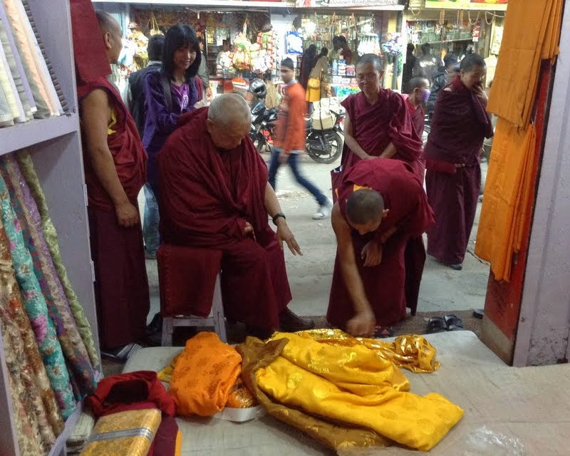 Lama Zopa Rinpoche in the market choosing the exact material to be offered this month and in future months to the Buddha statue inside the Mahabodhi Stupa, Bodhgaya, India, February 2014. Photo by Ven. Sarah Thresher.