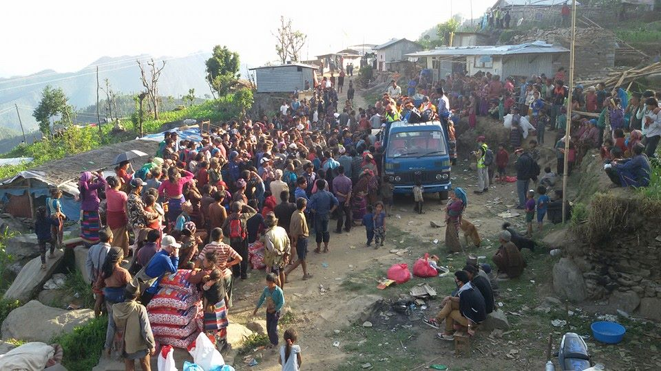 Villagers desperate for aid gather to receive much needed supplies.