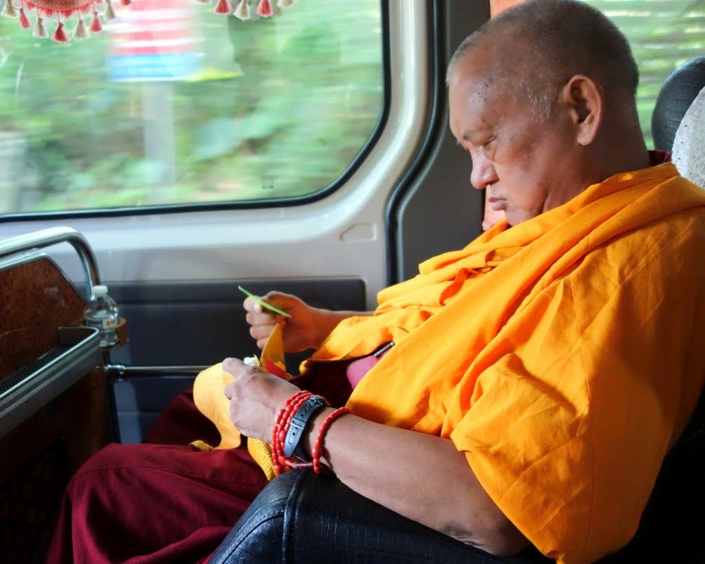 Lama Zopa Rinpoche reading texts on his way to the opening ceremony at Jinsiu Farlin in Taipei, Taiwan, April 2014. Photo by Ven. Roger Kunsang.