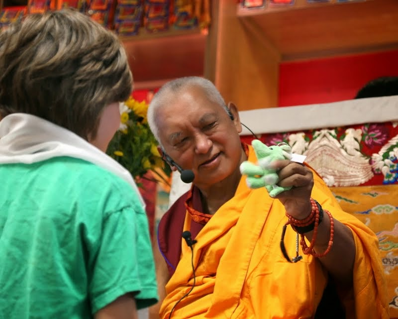 Lama Zopa Rinpoche offering a gift to a child at Kadampa Center, Raleigh, North Carolina, US, May 3, 2014. Photo by Ven. Thubten Kunsang.