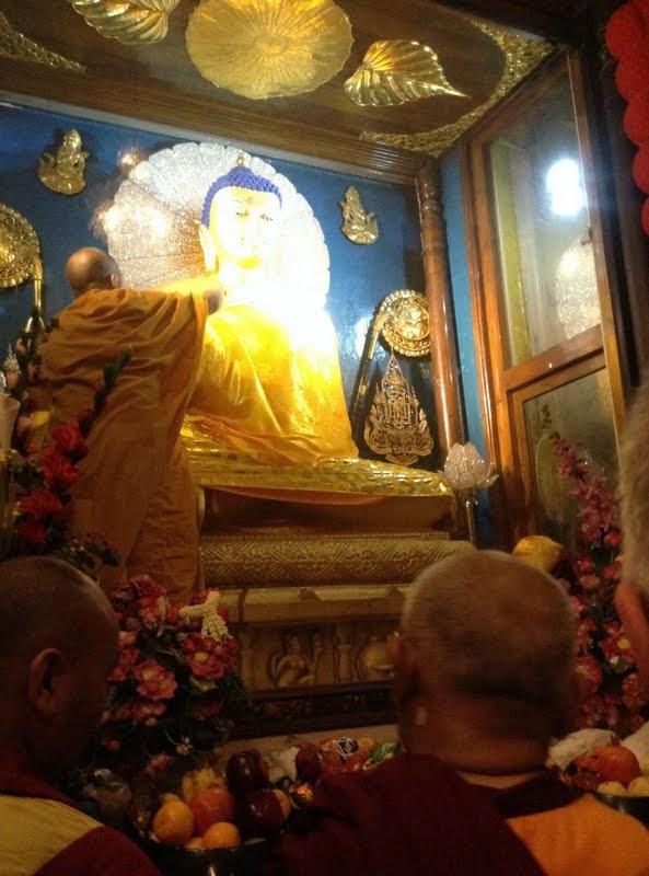 After chosing and blessing the material to be offered, Lama Zopa RinpochedidprayersastheBhanteofferedtherobestothe Mahabodhi StupaBuddhaveryslowlyandpreciselyeventhoughitwasabusyeveningwithmanypilgrims, Bodhgaya, India, February 2014. Photo by Ven. Sarah Thresher.