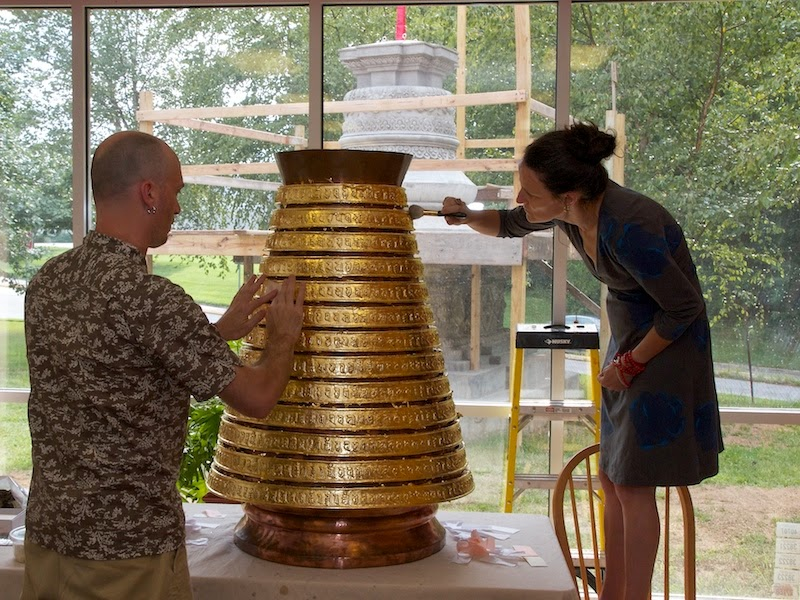 Troy applying gold leaf. Mer using a brush to push gold leaf into the crevices of the mantra characters on each of the disks.