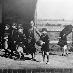 """Mrs. Albert William Smith with the Upton & Blewbury Cubs seeing them safely on their way to summer camp from Upton station. Approx 1934. Poster reads """"Travel Cheaper Still in 1935""""..."""