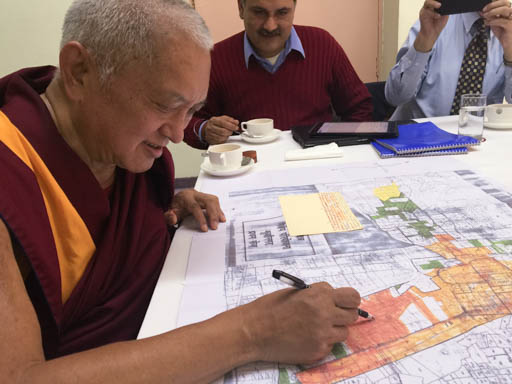 Lama Zopa Rinpoche looking over plans for Maitreya Buddha Kushinagar Project, Delhi, January 2015. Photo by Ven. Roger Kunsang.