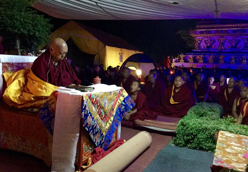 Rinpoche leading prayers at night for those who were injured or died in earthquake.