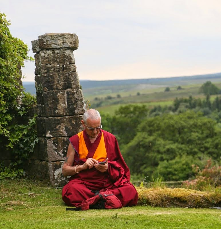 Ven. Roger Kunsang reading prayers on his mobile phone at Land of Joy, UK, July 2014. Photo by Ven. Thubten Kunsang.