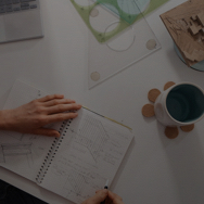 Overhead shot of woman sketching architectural plans in notebook at a desk