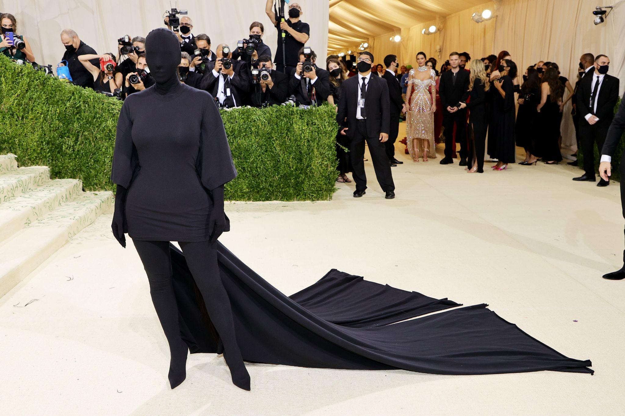 mulher usa roupa preta cobrindo toda a cabeça e rosto, braços, mãos e pés com uma cauda que arrasta no chão. Foto: Getty Images. Post Looks icônicos do VMA e Met Gala 2021.