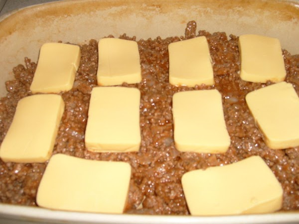 layer hamburger mixture and noodle mixture in casserole dish with the processed cheese between...