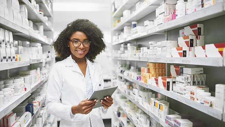 A imagem mostra uma atendente de farmácia sorrindo para a foto e fazendo o controle de estoque.