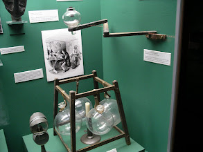 Photo: a folding arm wall lamp and a tatter's lamp. The glass globes were filled with water and would magnify the light of the candle