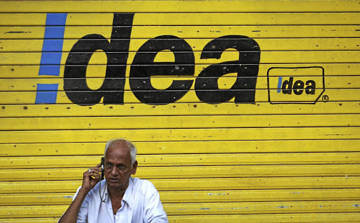 A man speaks on his cellphone in front of a shop displaying the Idea Cellular logo in Mumbai, India. Picture: REUTERS