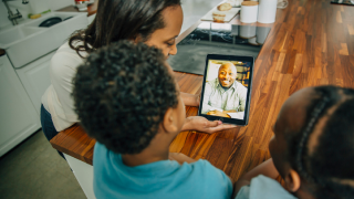 image of family gathered around tablet for video chat