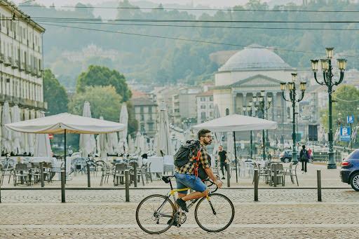Mattia pedals his bike across Turin's cobblestone streets