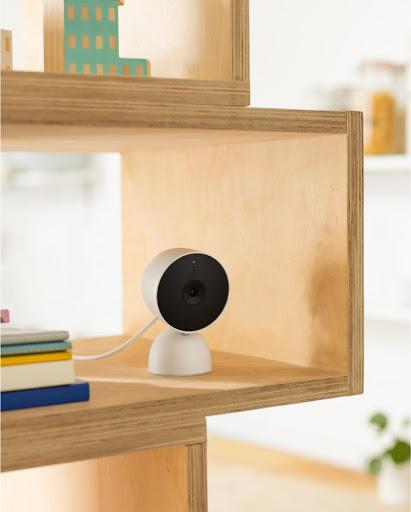 Una Nest Cam è posizionata su una mensola vicino ad altri oggetti del nucleo familiare.