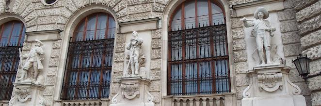 Photo: Skulpturen Neue Burg, Seite Heldenplatz  Von 1881 - 1914 dauerte die Bauzeit der Neuen Burg. Der halbkreisförmige Flügel mit einer großen Freitreppe in der Mitte ist mit 20 Skulpturen geschmückt.  Sie repräsentieren einige Epochen der österreichischen Geschichte, die glorreiche Barockzeit ist erstaunlich wenig präsent.  Das Konzept geht auf einen Sektions-Chef zurück, der sich gegen Carl Hasenauer durchsetzte. Dieser plante nämlich 20 Habsburgerstatuen aufzustellen.  Die Figuren von links nach rechts und ihre Bildhauer:
