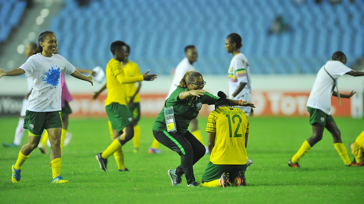 Banyana Banyana head coach Desiree Ellis celebrates with her midfield pairing of Jermaine Seoposenwe (R) and Leandra Smeda (L) after their 2-0 Caf Women's Cup of Nation semifinal win over Mali on November 27 2018 at Cape Coast Stadium in Accra, Ghana.