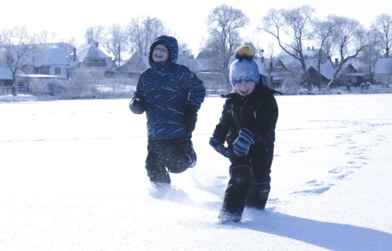 Zēni bauda ziemas priekus - skrien pa sniegu.
