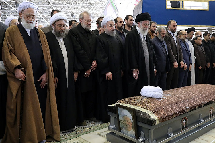 Iran's supreme leader Ayatollah Ali Khamenei and Iranian President Hassan Rouhani pray next to the coffin of former president Akbar Hashemi Rafsanjani during his funeral ceremony in Tehran, Iran, on Tuesday. Picture: REUTERS/HANDOUT