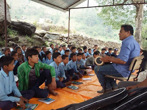 Photo: Mr. Tamang teaching the children to play Madal