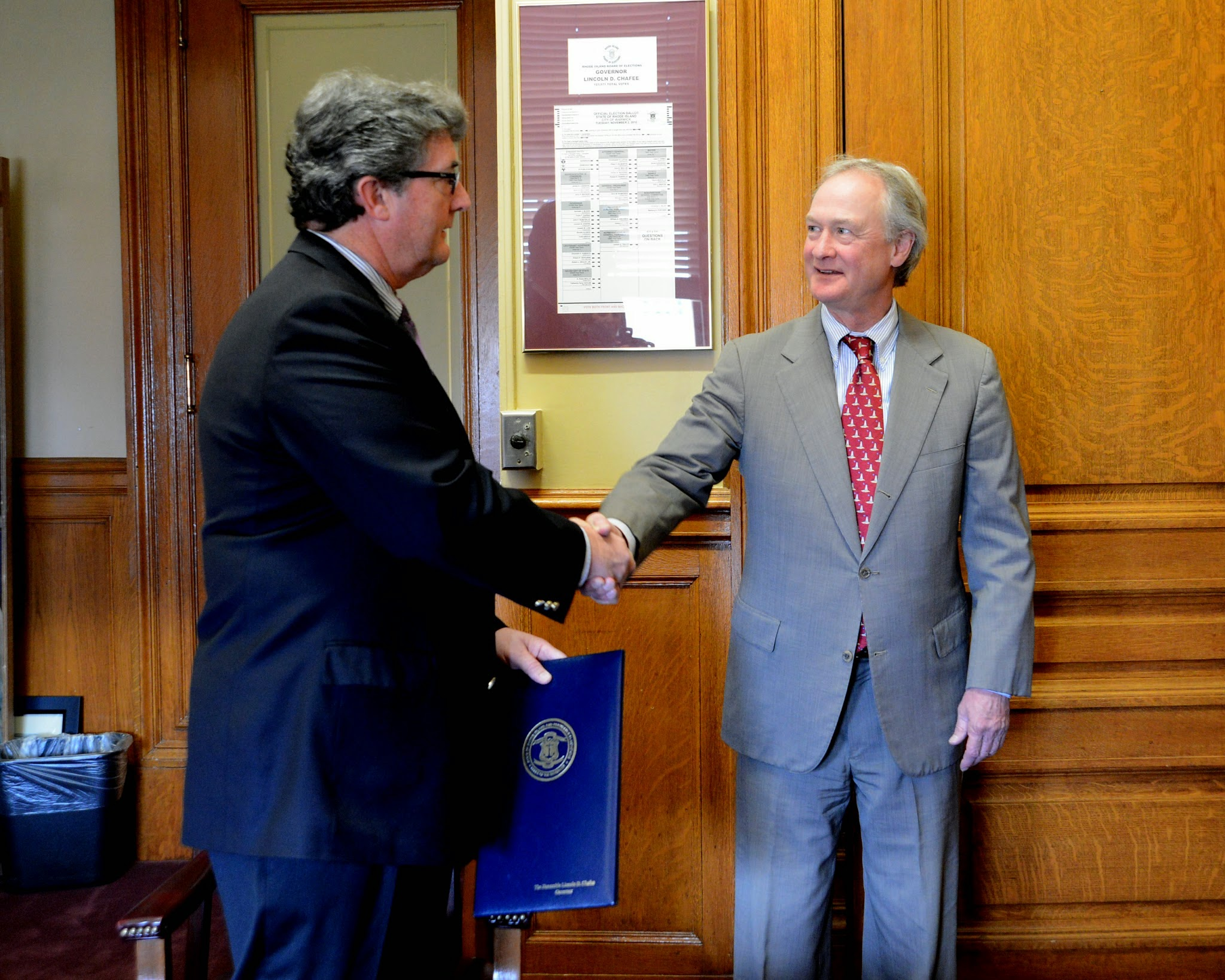 Photo: Rep. Robert Craven is congratulated by Governor Lincoln Chafee after signing his bill on May 6, 2014.  Rep. Craven's legislation saved a $6 million federal grant awarded to the Quonset Development Corporation by the federal government.