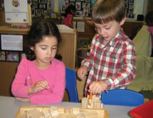 A boy and girl play with blocks at a table together.