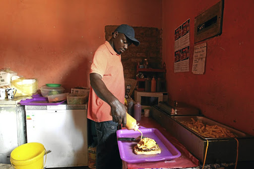Hassan Kajaja, the owner of Panini Cafe, prepares a panini based meal at his shop in Atteridgeville.
