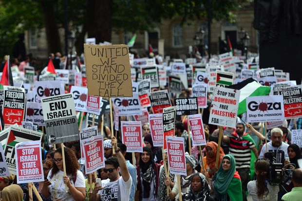 Protesters display placards and banners as they take part in a demonstration against Israeli airstrikes in Gaza in central London on July 19, 2014. Image: CARL COURT/AFP/Getty Images)