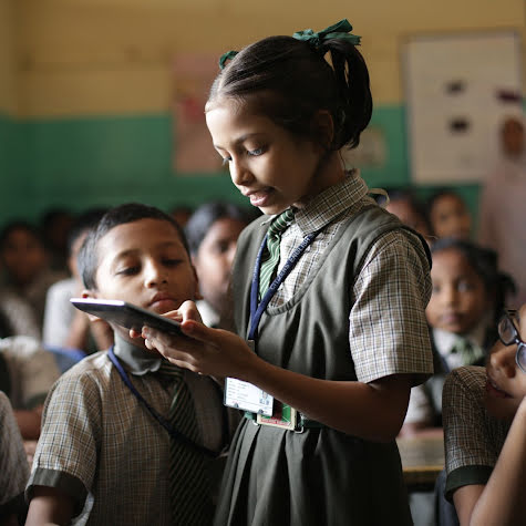 A young girl holding a tablet while classmates crowd around.