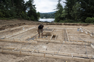 Photo: We have to tie in the verts and there is just no nice way to do it.  Kyle just dug out under a hold down bolt.  The grids in the expanded footings don't look good now, but we tied them up and as the concrete is placed in the lower half of the footing, we'll cut it loose and set it in place.
