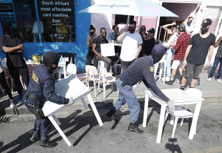 Police move tables and chairs from the street as chefs, waiters, winery workers, hoteliers and tourism operators protest for #JobsSaveLives in Cape Town's CBD on July 22 2020.