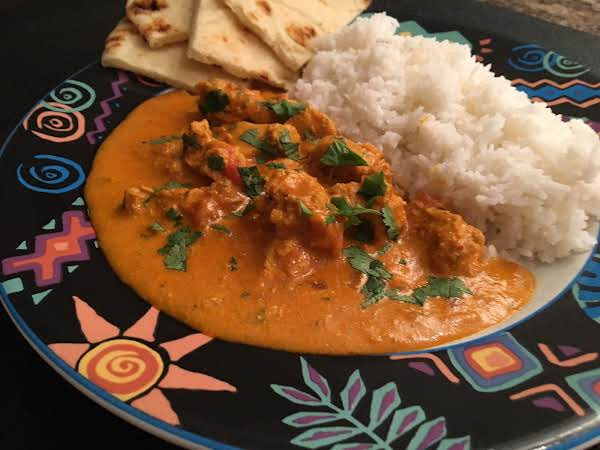 Chicken In An Orange Sauce On A Plate Along With Naan Bread And White Rice.